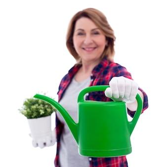 白い背景で隔離の女性の庭師の手でじょうろ-缶に焦点を当てる