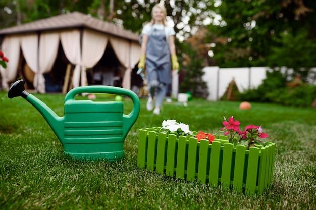 庭のじょうろ、エプロンと手袋の女性。女性の庭師は、屋外の植物、ガーデニングの趣味、花屋のライフスタイルとレジャーの世話をします