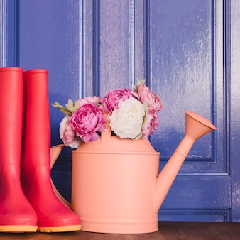 Watering can with roses next to gumboots