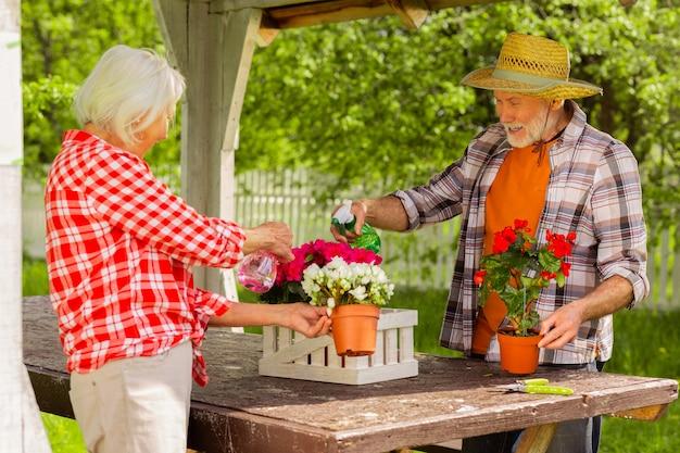함께 꽃을 급수. 함께 꽃에 물을 주면서 즐거운 느낌을 보내는 쾌활한 연금 수령자의 커플