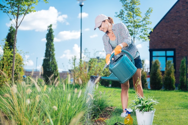 Watering garden bed. blonde-haired woman wearing peaked cap and comfortable casual clothes watering her garden bed