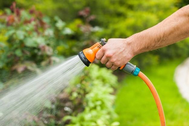 야외 호스로 물을 주는 녹색 정원
