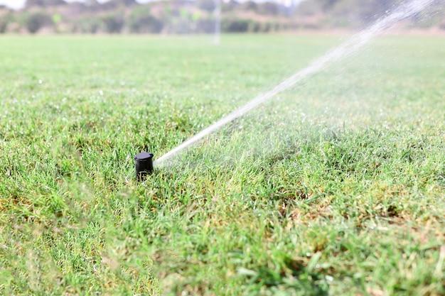 Полив зеленой травы спринклерной системой во время засухи
