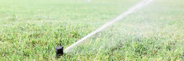 干ばつの間にスプリンクラーシステムで緑の草に水をまく