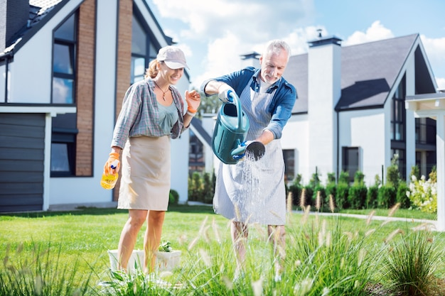 Watering plants. bearded grey-haired man holding big garden sprinkler while watering plants with his beautiful happy wife