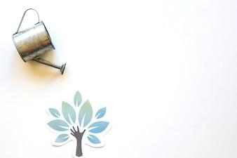 Watering pot over paper tree
