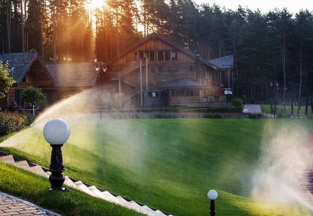 Полив газона возле деревянного дома летним утром