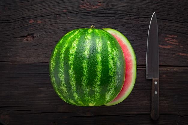 スイカと木製のテーブルの上のナイフ