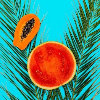 Арбуз и папайя на синем фоне. плоская планировка минимального веганского искусства