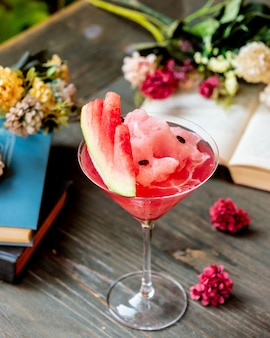Watermelon cocktail with fruit and flowers.