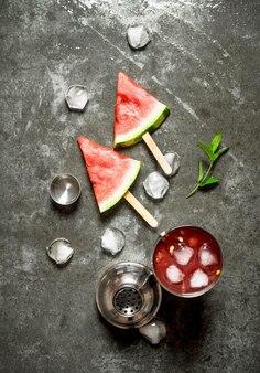 石のテーブルのシェーカーで氷とスイカのカクテル。