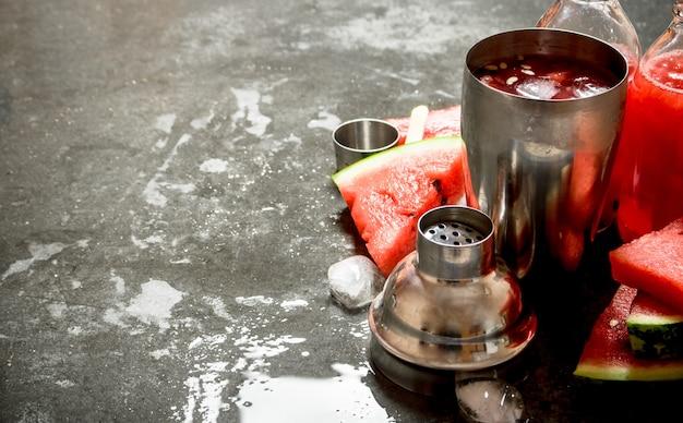 石のテーブルのシェーカーで氷とスイカのカクテル