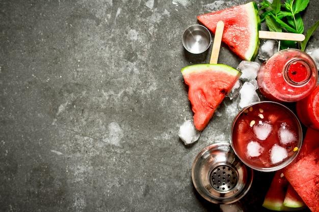 シェーカーで氷とスイカのカクテル。石のテーブルの上。
