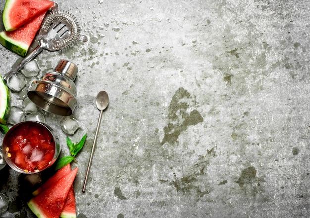 シェーカーにミントと氷を入れたスイカカクテル。石のテーブルの上。