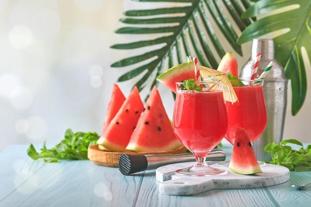 민트와 얼음을 곁들인 수박 칵테일. 푸른 나무 테이블에 안경에 여름 상쾌한 음료. 건강한 여름 식사의 개념입니다.