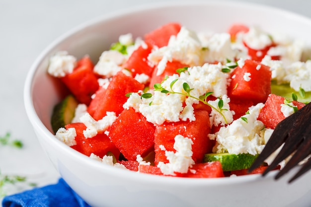 Watermelon, cucumber and feta cheese salad in white bowl.