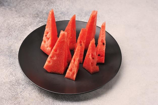 Нарезанный кусочками арбуз на черной тарелке