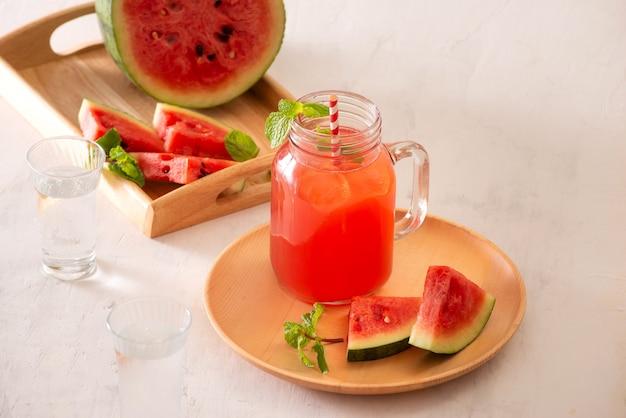 Напиток из арбуза в стакане с кусочками арбуза на белой поверхности