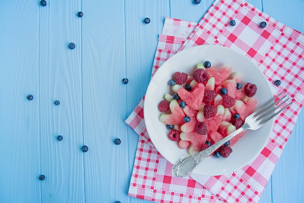 Watermelon in the form of hearts, raspberries, blueberries in a white plate.