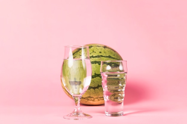 Watermelon and glasses on pink background