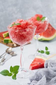 ミントとスイカの花崗岩、灰色のコンクリートの背景にガラスの夏のさわやかな飲み物。セレクティブフォーカス。