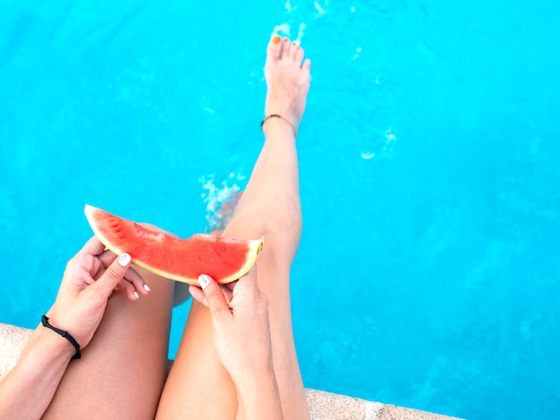 Watermelon in the hand of a girl at a swimming pool