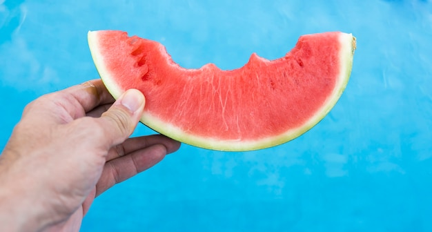 Watermelon in the hand of a man at a swimming pool