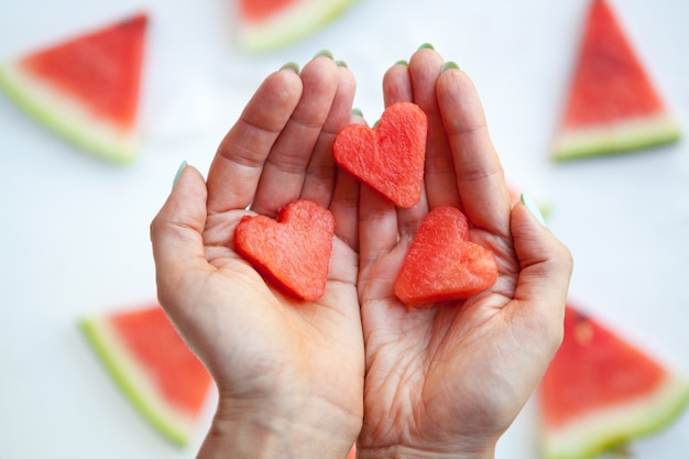Watermelon hearts slices on womans hands flat lay watermelon slice on white love and care concept