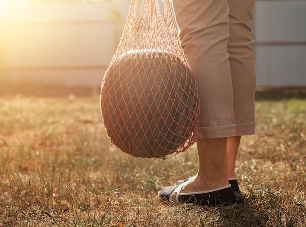 Арбуз в эко-авоське в руках женщины-фермера, несущей его на открытом воздухе