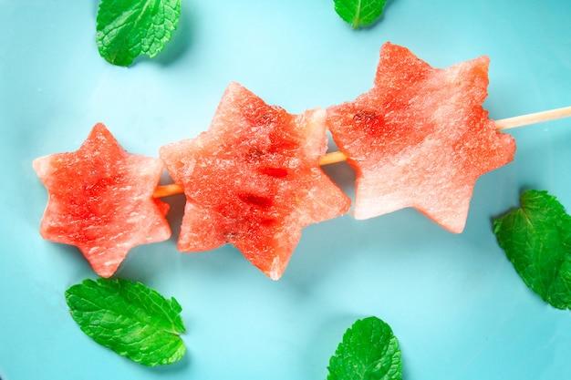 ミントの葉と串焼きの星の形のスイカは青いプレートにあります。 Premium写真
