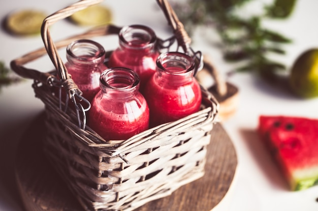 ミントの葉とライムの柑橘類のバスケットが付いている瓶のスイカジュース