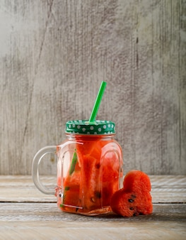 Watermelon juice smoothie in a mason jar with slice of watermelon and swirled straw side view on wooden and grunge background