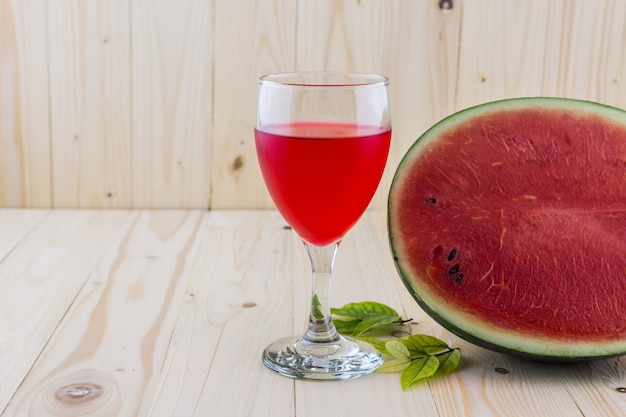 Watermelon juice in a wine glass with half water melon on wood floor background