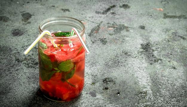 素朴なテーブルの上のガラスの瓶にミントとスイカジュース。