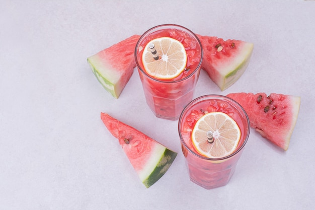 Watermelon juice with red fruit slices on white.