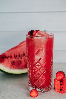 Watermelon lemonade with strawberry on a wooden table