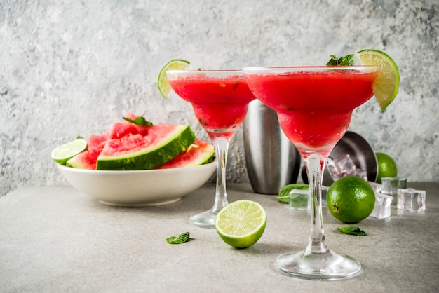 Watermelon margarita cocktail with lime and sliced watermelon