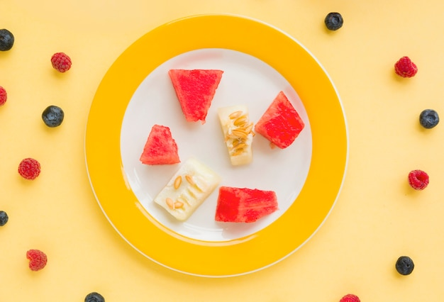 Watermelon and muskmelon slices on plate with raspberries and blueberries on yellow backdrop