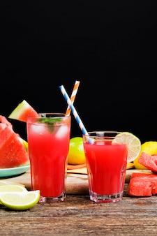 수박 천연 주스와 테이블에 얇게 썬 붉은 육즙 수박 덩어리, 천연 식품, 생태 학적으로 재배 된 붉은 수박과 레몬과 라임의 클로즈업