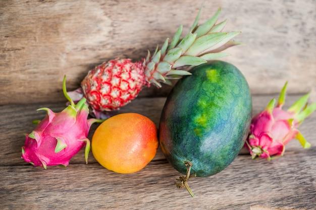 古い木製の背景にマンゴーパイナップルとドラゴンフルーツの近くのスイカ