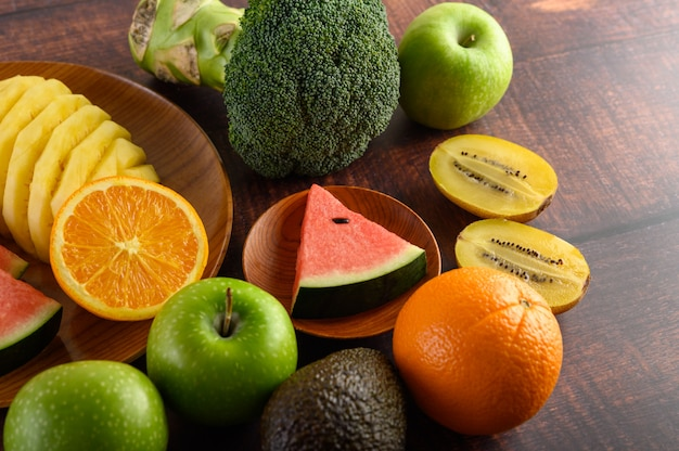 Watermelon, orange, pineapple, kiwi cut into slices with apples and broccoli on a wooden plate and wooden table.