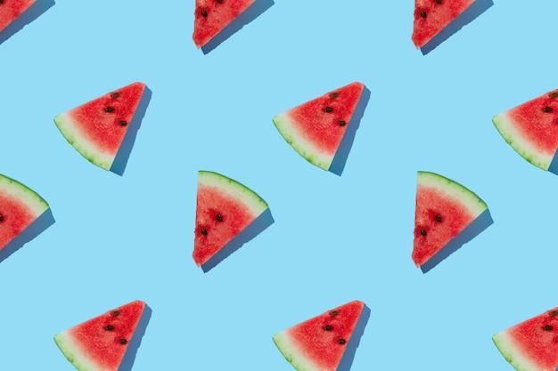 Watermelon pattern made of sliced watermelon on blue background.