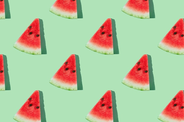 Watermelon pattern made of sliced watermelon on mint green background.
