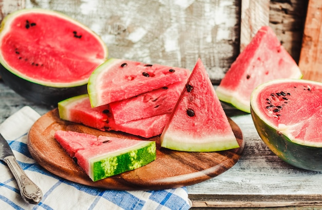 Watermelon and pieces of fruit on wood