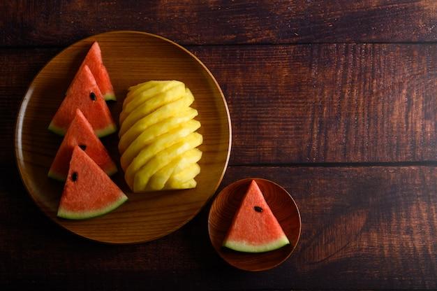 L'anguria e l'ananas hanno tagliato a pezzi su un piatto di legno