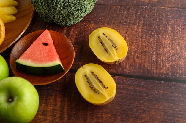 Watermelon, pineapple, kivi, cut into pieces with apples and broccoli on a wooden plate.