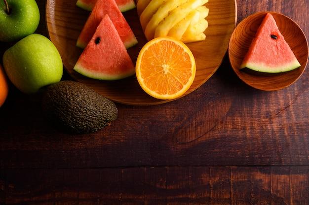 Арбуз, ананас, апельсины, нарезанные на кусочки с авокадо и яблоками на деревянный стол. вид сверху.