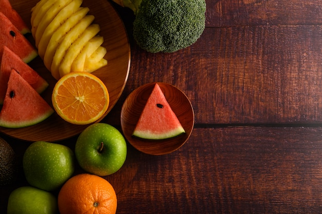 Арбуз, ананас, апельсины, нарезать кусочками авокадо, брокколи и яблоки на деревянный стол. вид сверху.