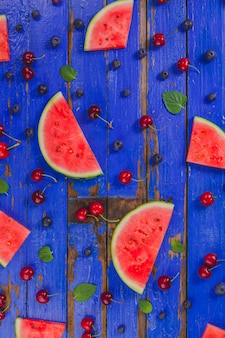 Watermelon portions and other fruits on blue wooden surface