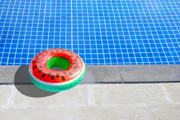 Резиновое кольцо «арбуз» для плавания на цементном полу бассейна. летний фон концепция